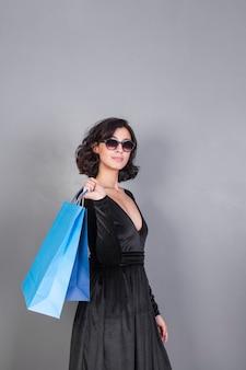 Mulher, em, vestido preto, com, azul, bolsas para compras