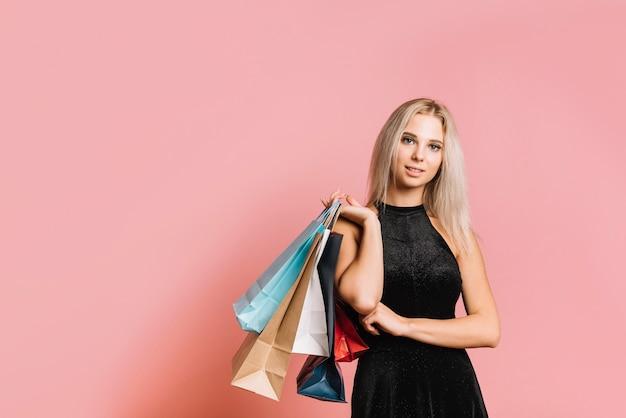 Mulher, em, vestido preto, ficar, com, bolsas para compras