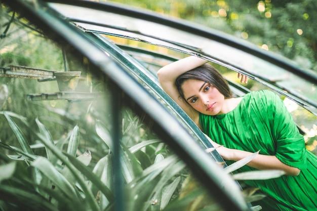 Mulher, em, vestido verde, olhando câmera
