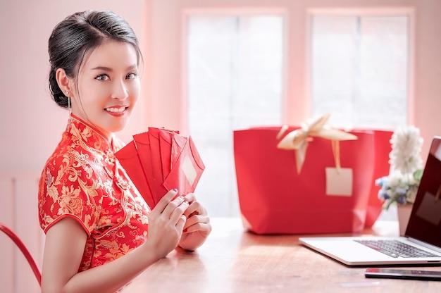 Mulher, em, vestido vermelho, cheongsam tradicional, segurando, envelopes vermelhos, e, usando computador portátil