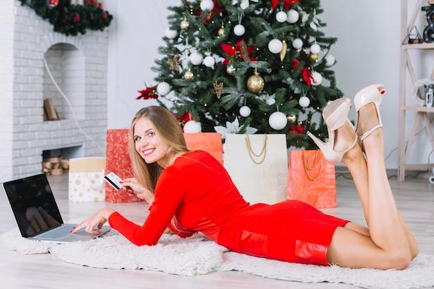 Mulher, em, vestido vermelho, mentindo chão, com, laptop, e, cartão