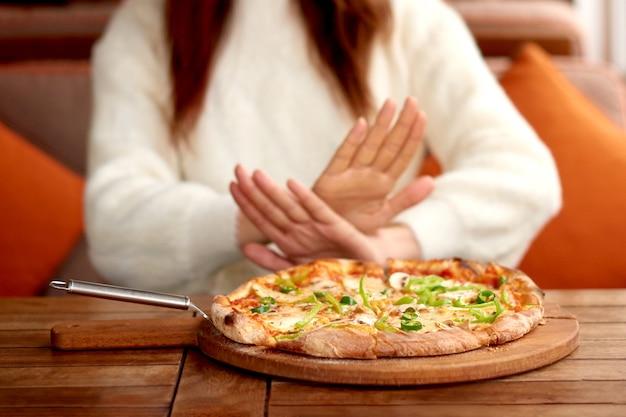 Mulher emagrecedora recusa-se a assar alimentos e alimentos gordurosos. mulher fazendo dieta ou nutrição adequada