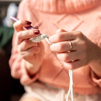 Mulher embaçada fazendo crochê dentro de casa