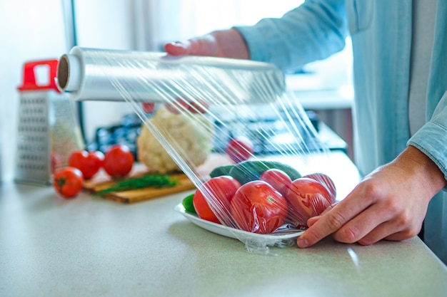 Mulher embalada legumes frescos usando filme alimentar para armazenamento de alimentos