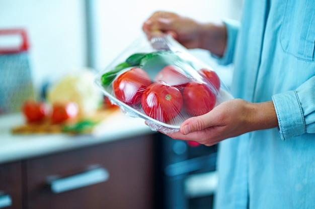 Mulher embalada legumes frescos usando filme de alimentos para armazenamento de alimentos na geladeira