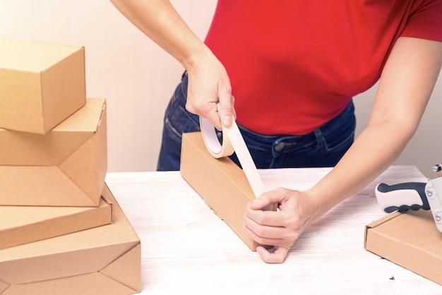 Mulher embalagem caixas de papelão usando fita