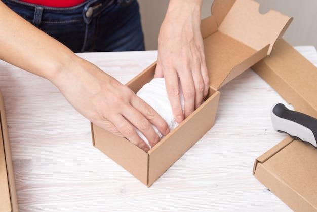 Mulher embalando caixas de papelão, produtos de picking e puttind