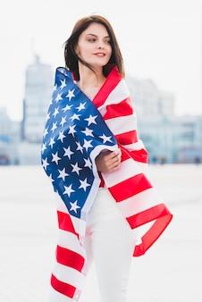 Mulher, embrulhado, em, bandeira americana, patrioticamente, olhar, ao longo, quadrado