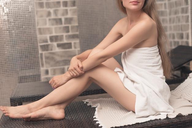 Mulher, embrulhado toalha, sentando, ligado, deckchair, em, spa