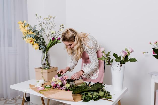 Mulher embrulhando buquê de flores