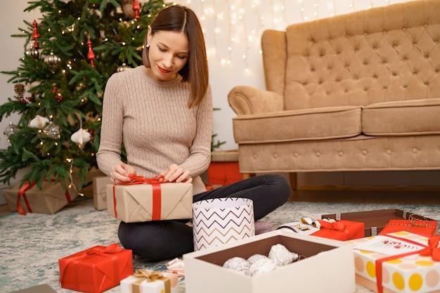 Mulher embrulhando um presente de natal enquanto está sentada no carrinho na sala de estar