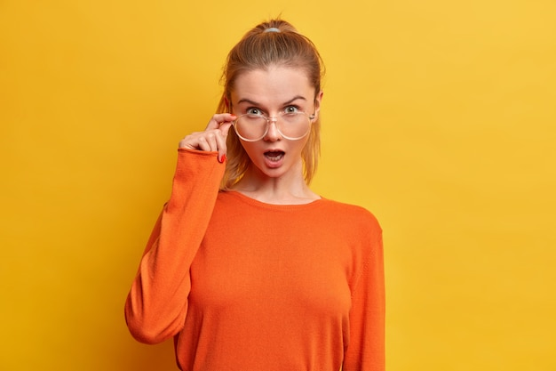 Mulher emocionada e surpresa com a boca aberta parece através de óculos ópticos, vestida com um macacão laranja casual, ouve notícias surpreendentes, poses