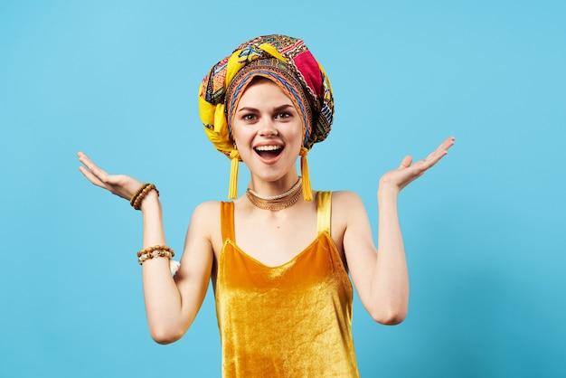 Mulher emocional alegre turbante multicolorido vestido amarelo parede decoração azul.