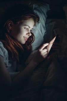 Mulher emocional com o telefone nas mãos à noite deitada na cama, vício em tecnologia
