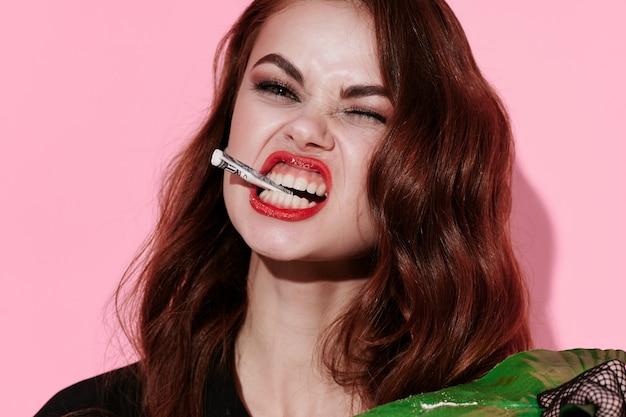 Mulher emocional com objeto nos dentes fundo rosa maquiagem brilhante