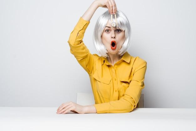 Mulher emocional com peruca branca sentada à mesa de rolos de sushi