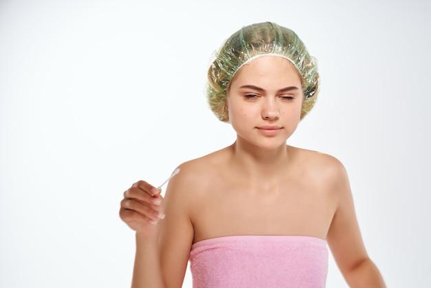 Mulher emocional com toalha rosa ombros nus e problemas de pele dermatologia