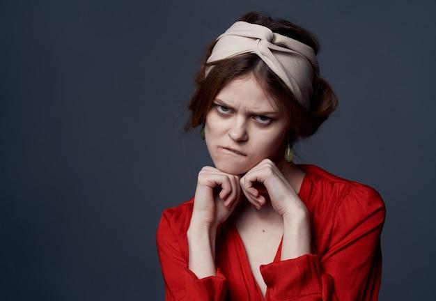 Mulher emocional com turbante vestido vermelho na cabeça enfeita o fundo cinza