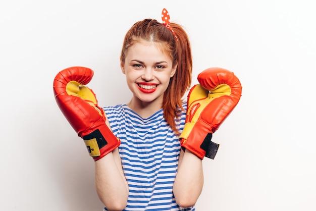 Mulher emocional com uma camiseta listrada e luvas de boxe rindo em um fundo claro