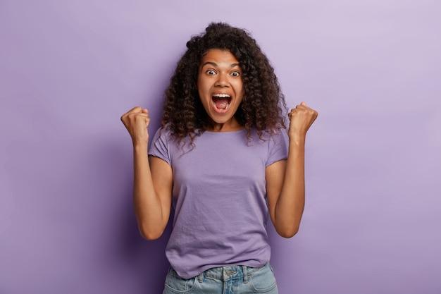 Mulher emocional de pele escura com cabelo afro, levanta os punhos cerrados, exclama com entusiasmo, regozija-se com o doce sucesso, sente o gosto da vitória, grita pelo time favorito, veste camiseta roxa e jeans