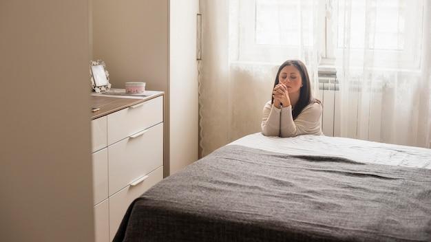 Mulher emocional dizendo uma oração em casa