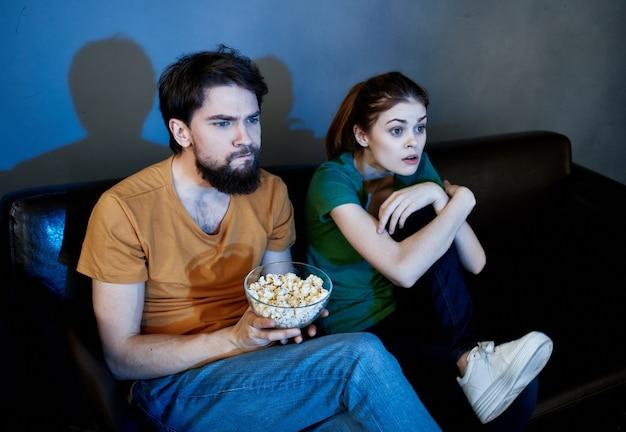 Mulher emocional e homem no sofá com pipoca assistindo tv