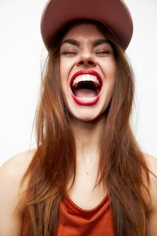 Mulher emocional em um boné emoções divertidas risada olhos fechados noite maquiagem vista cortada