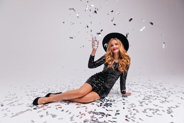 Mulher emocional em vestido curto sentado em confete de brilho. alegre menina caucasiana com elegante chapéu comemorando algo.
