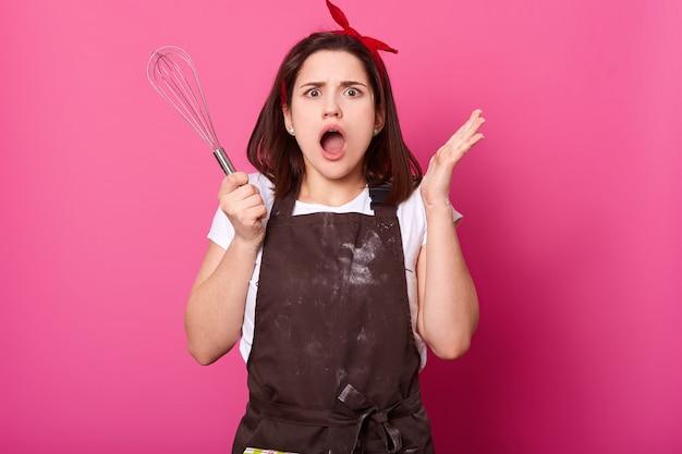 Mulher emocional energética usa avental desarrumado marrom escuro, camiseta branca, acessórios, coloca as mãos segurando o batedor. jovem chocada cheia de indignação enquanto praticava habilidades culinárias.