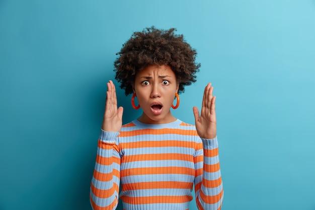 Mulher emocional estupefata impressionada pelo tamanho grande, levanta palmas e mostra algo enorme, abre boca e explica, molda objeto invisível, abre os braços, vestida de suéter listrado, isolado no azul