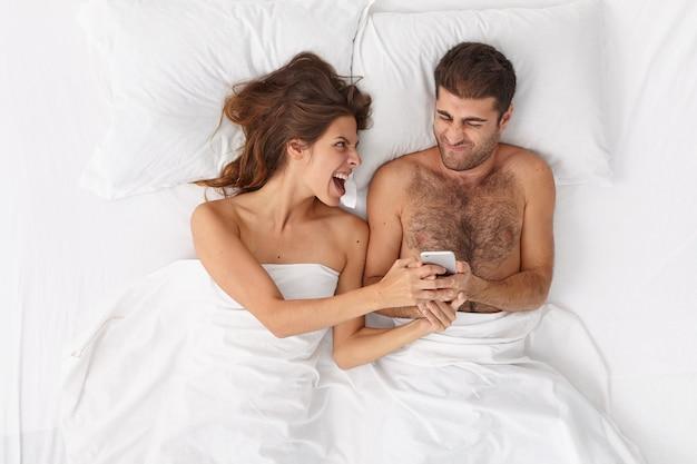 Mulher emocional exclama e mostra algo ao marido no celular, fiquem na cama juntos, descanse pela manhã. jovens cônjuges viciados em tecnologias modernas lêem notícias ou assistem a vídeos online.