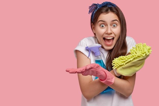 Mulher emocional feliz cruza as mãos, segura o esfregão e o limpador em spray, usa uma camiseta branca e luvas, feliz por terminar o trabalho doméstico a tempo, não atrasado para o encontro, posa contra a parede rosa. bom humor para limpar