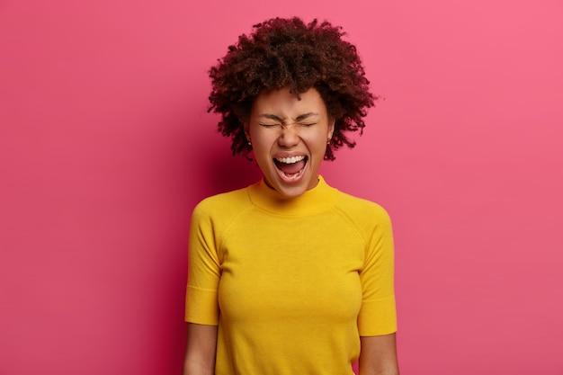 Mulher emocional fica com a boca bem aberta, grita e berra alto, não consegue controlar suas emoções, estar com raiva de alguém, usa camiseta amarela, isolada na parede rosa, reprova alguém
