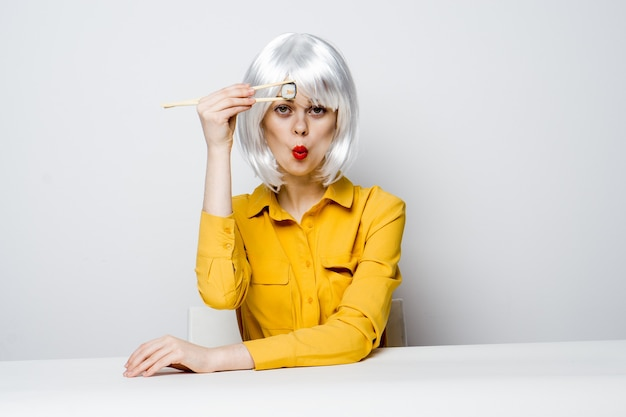 Mulher emocional na peruca branca se senta à mesa de rolos de sushi. foto de alta qualidade