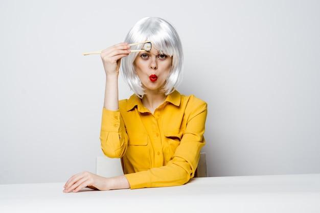 Mulher emocional na peruca branca se senta à mesa de rolos de sushi.