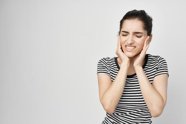 Mulher emocional segurando rosto com luz de fundo para dor de dente
