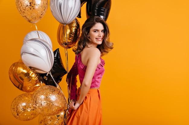 Mulher emocional segurando um monte de balões de festa