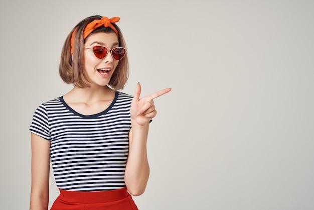 Mulher emocional usando óculos escuros camiseta listrada estilo moderno posando com luz de fundo