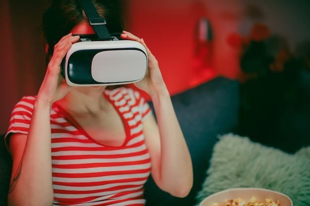 Mulher emocional usar vr fone de ouvido jogando videogame. mulher relaxante jogando videogame usando o fone de ouvido vr. jogador feminino caucasiano