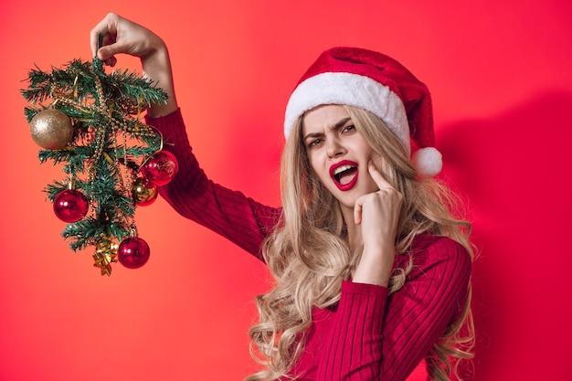 Mulher emocional vestida de fundo rosa de brinquedos de árvore de natal de papai noel. foto de alta qualidade