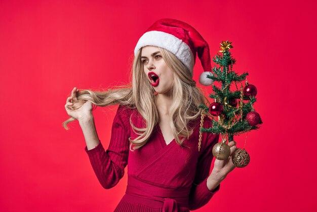 Mulher emocional vestida de papai noel, árvore de natal, brinquedos fundo rosa