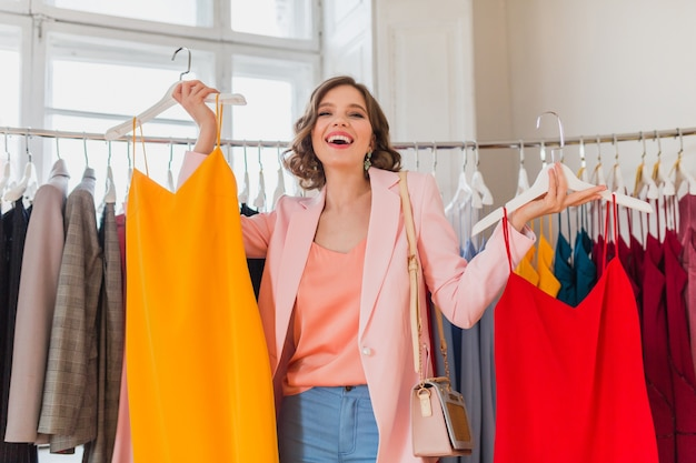 Mulher emocionalmente atraente e feliz segurando vestidos coloridos em uma loja de roupas
