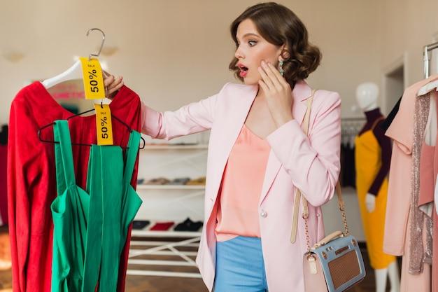 Mulher emocionalmente atraente segurando vestidos coloridos em um cabide em uma loja de roupas
