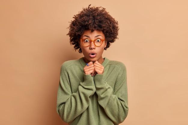 Mulher emocionalmente chocada com cabelo encaracolado segura a respiração, mantém as mãos juntas, abre a boca com espanto e olha os olhos arregalados, vestida com jaqueta casual e modelos de óculos ópticos internos