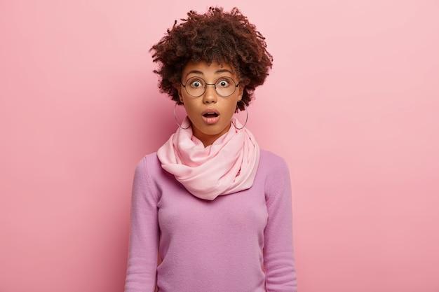 Mulher emocionalmente estupefata com penteado afro encaracolado, mantém a boca aberta, usa óculos redondos, macacão casual, chocada com notícias intrigantes, abre a boca de admiração