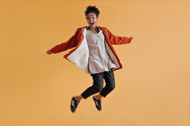 Mulher empolgada com um blusão laranja pulando na parede amarela