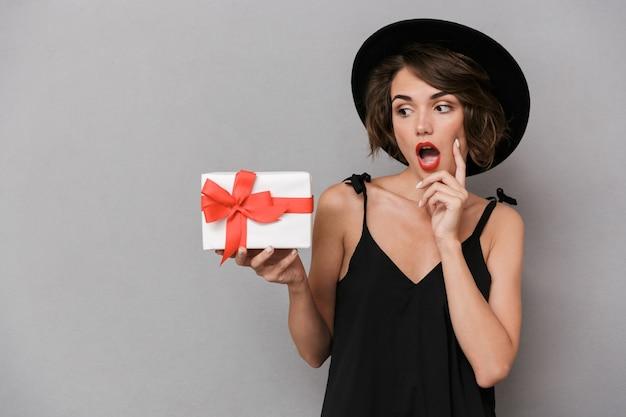 Mulher empolgada com vestido preto e chapéu segurando uma caixa de presente, isolada sobre uma parede cinza