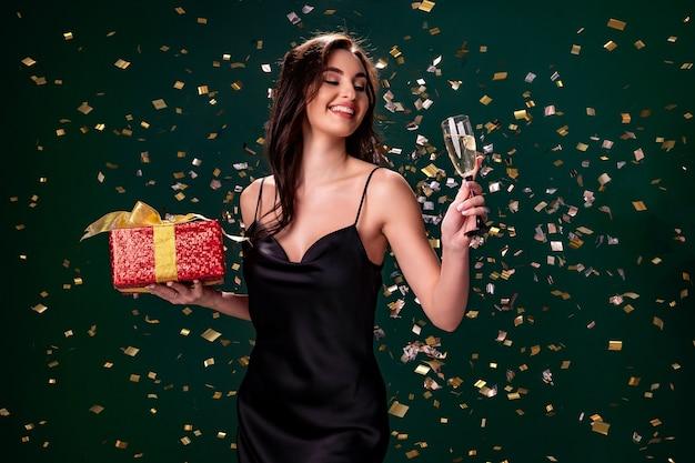 Mulher empolgada de vestido preto segurando caixa vermelha de presente e taça de champanhe. Foto Premium