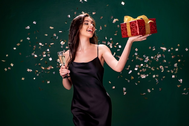 Mulher empolgada de vestido preto segurando caixa vermelha de presente e taça de champanhe.