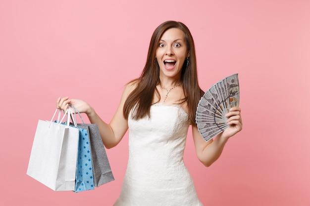Mulher empolgada em um vestido branco segurando um pacote de muitos dólares, dinheiro à vista, sacolas coloridas com compras após as compras